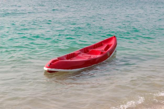 Petit bateau rouge sur la plage.
