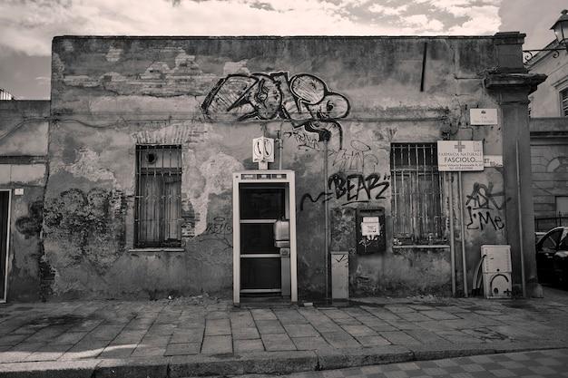 Petit bâtiment en décomposition couvert de graffitis pris dans une ruelle de la ville de cagliari