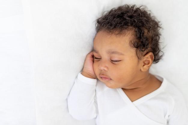 Un petit bébé afro-américain dort sur un lit blanc à la maison avec sa main pliée sous sa joue