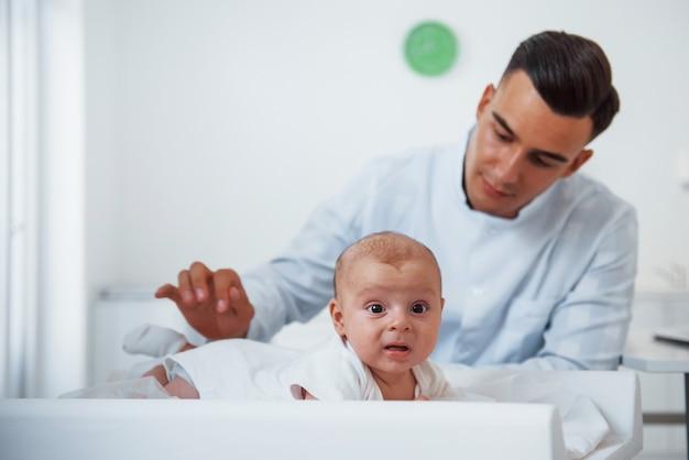 Petit bébé allongé sur la table. le jeune pédiatre est à la clinique pendant la journée.