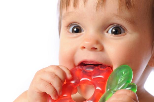 Petit bébé d'un an tient sur place jouet de dentition coloré.