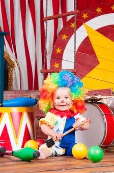 Petit bébé clown avec perruque multicolore nez rouge avec des boules.