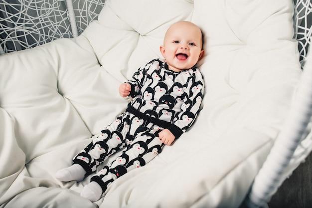 Petit bébé couché sur une balançoire ronde et souriant