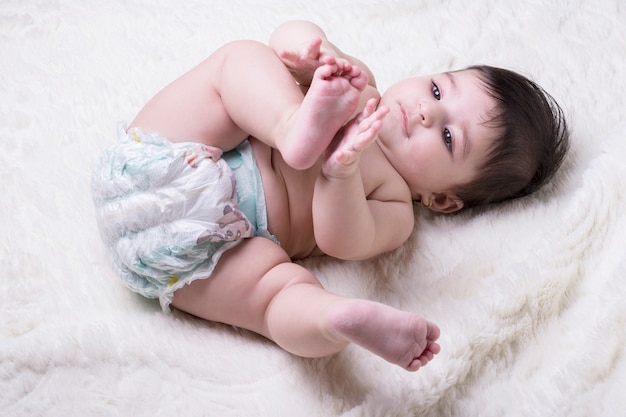 Petit bébé couché sur une couverture moelleuse blanche et tenant sa jambe