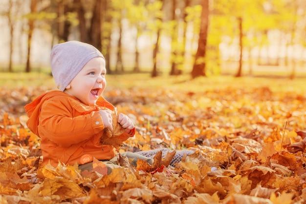 Petit bébé dans le parc d'automne ensoleillé