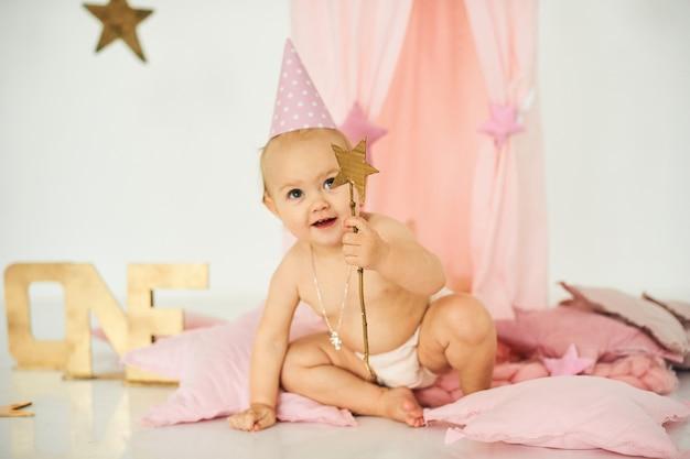 Un petit bébé dans une tente rose avec une baguette magique près d'un gros gâteau. concept de fête d'anniversaire