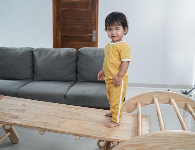 Petit bébé debout sur des jouets triangulaires pikler tout en jouant à la maison