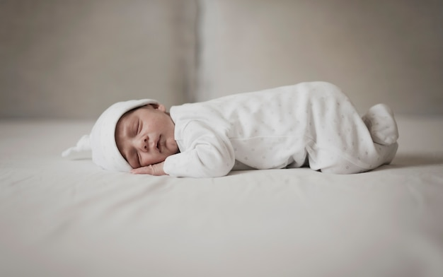 Petit bébé dort sur des draps blancs