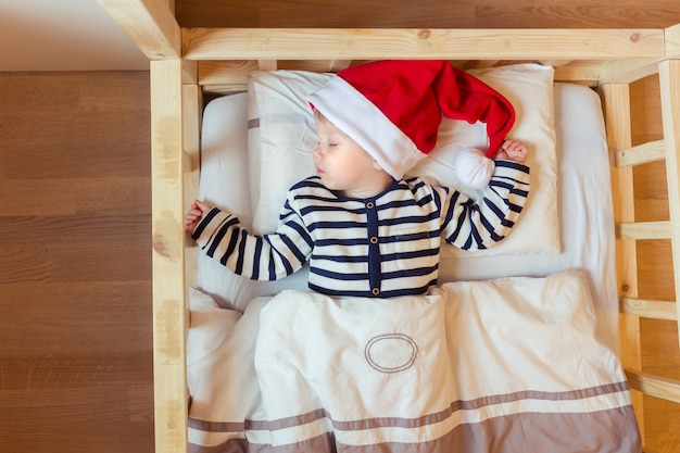 Un petit bébé dort sur un lit blanc dans un chapeau de père noël rouge avant la nuit de noël