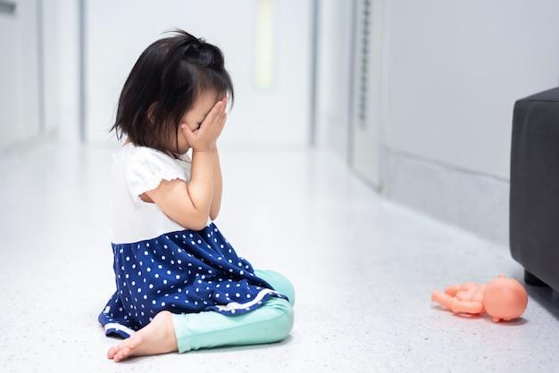 Petit bébé enfant assis sur le sol en pleurant et couvrant son visage avec sa main