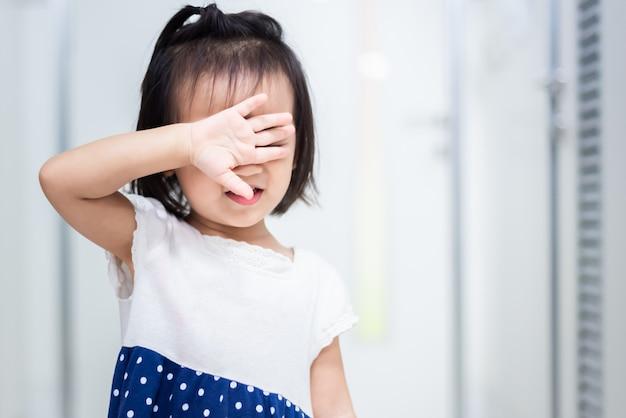 Petit bébé enfant tenant une poupée craignant de sortir par la porte