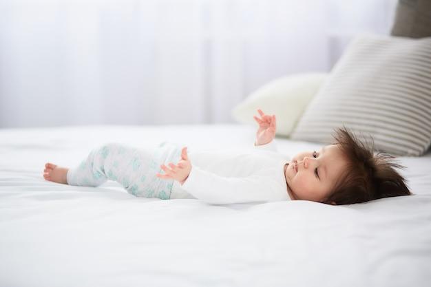 Le petit bébé est allongé sur le lit