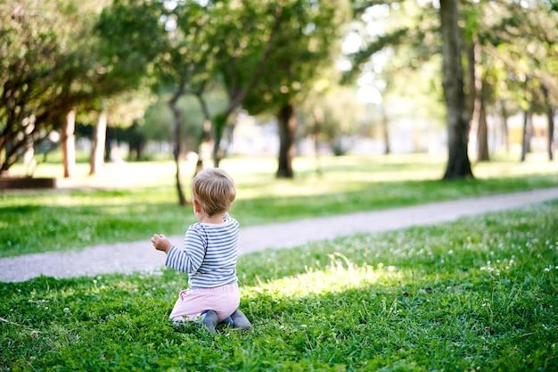 Petit bébé est assis sur ses genoux sur une pelouse verte près de la vue arrière de la passerelle