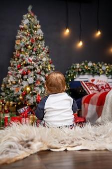 Petit bébé est assis sur un tapis moelleux et regarde l'arbre de noël