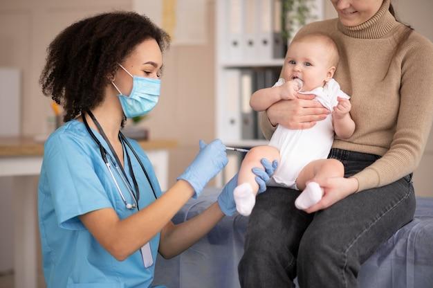 Petit bébé étant à la clinique de santé pour la vaccination