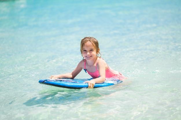 Petit bébé femme jeune surfeur avec bodyboard s'amuse