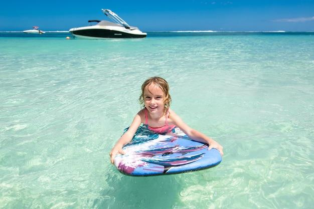 Petit bébé femme jeune surfeur avec bodyboard