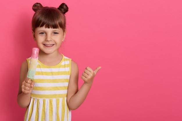 Petit bébé fille enfant tenant la crème glacée dans les mains posant isolé sur rose
