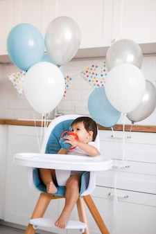 Petit bébé garçon assis dans une chaise haute bleue à la maison sur la cuisine blanche et l'eau potable de la tasse sippy