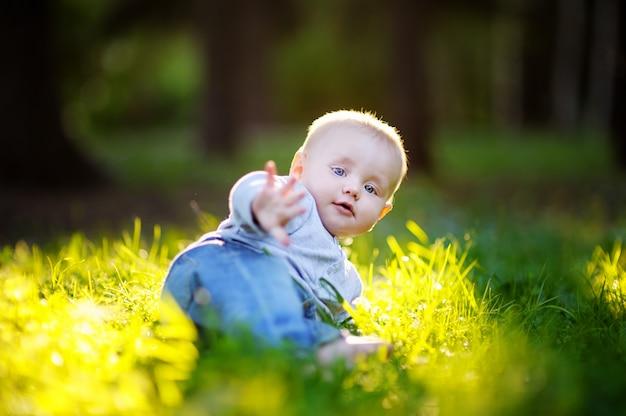Petit bébé garçon au parc ensoleillé