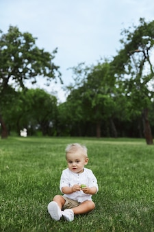 Petit bébé garçon en chemise blanche assis sur l'herbe
