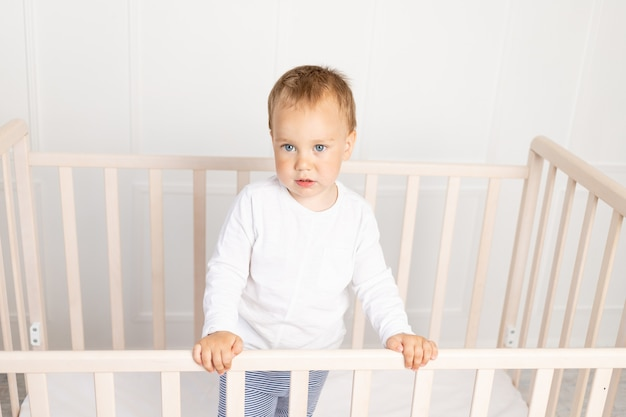 Petit bébé garçon dans la crèche en regardant la caméra dans la chambre des enfants lumineux