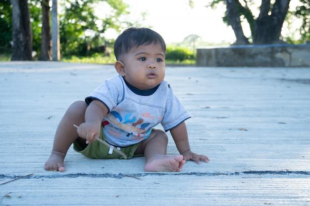 Petit bébé garçon joue du bois de bâton sur le parc