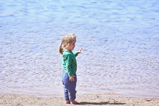 Petit bébé garçon à la plage de la mer ou de l'océan enfants vacances d'été en plein air enfance et bonheur