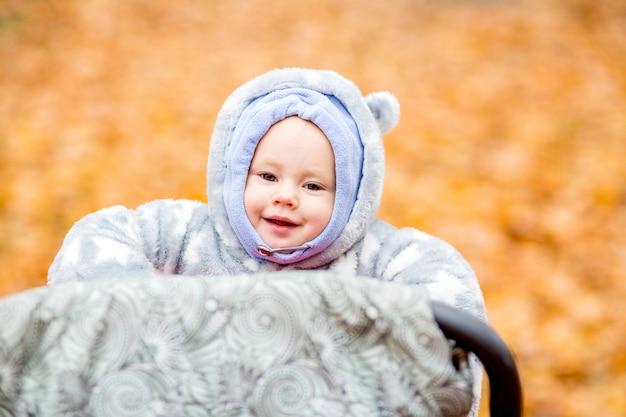 Petit bébé joue dans le parc d'automne petite fille avec chêne et feuille d'érable feuillage d'automne