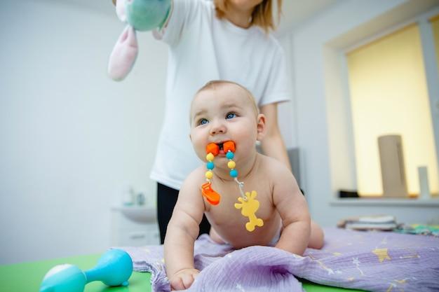 Un petit bébé avec un jouet dans la bouche se fait masser dans une salle de massage, le masseur le distrait avec ...