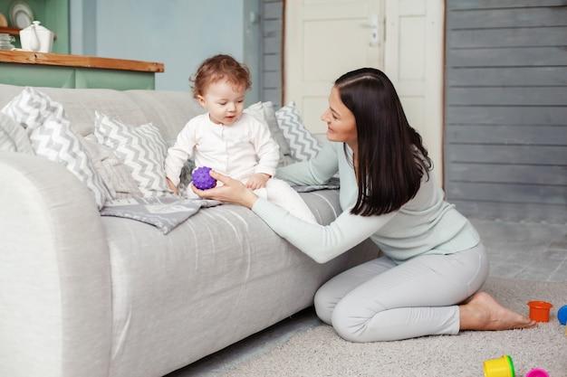 Petit bébé et maman jouent dans la chambre sur le canapé avec des boules de caoutchouc brillantes