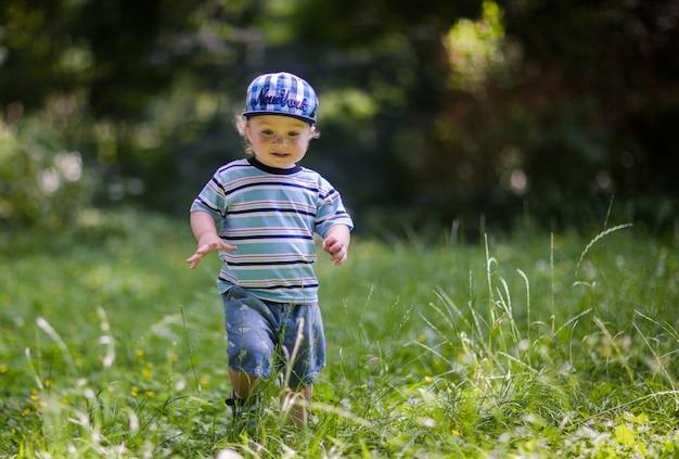 Petit bébé mignon marche sur l'herbe