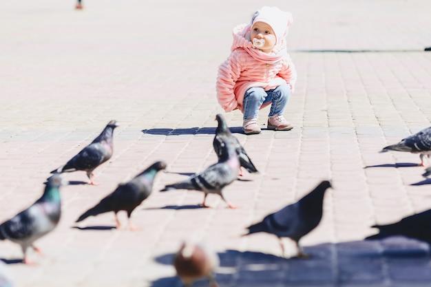 Petit bébé mignon marche sur la place avec des oiseaux