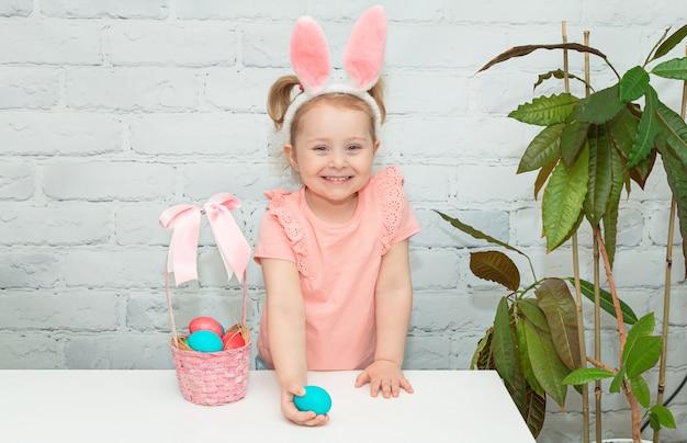 Le petit bébé mignon porte des oreilles de lapin le jour de pâques petite fille avec des oeufs de pâques
