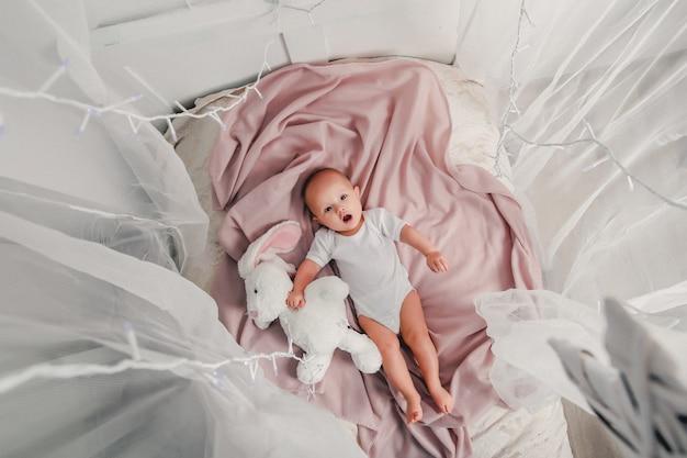 Un petit bébé s'allonge sur un lit avec un lapin en peluche et sourit