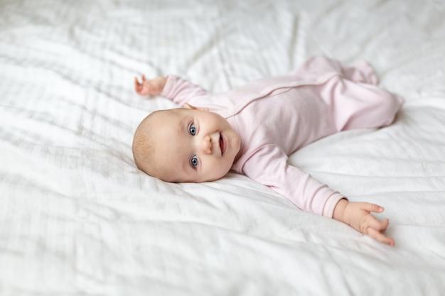 Un petit bébé sourit allongé sur le lit sur un drap blanc dans la chambre des parents