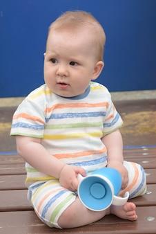 Petit bébé avec tasse d'eau