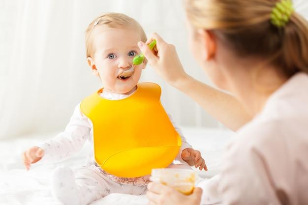 Petit bébé tétant avec une cuillère