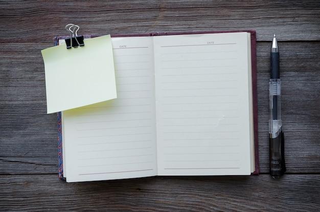 Petit bloc-notes avec un stylo sur fond de bois