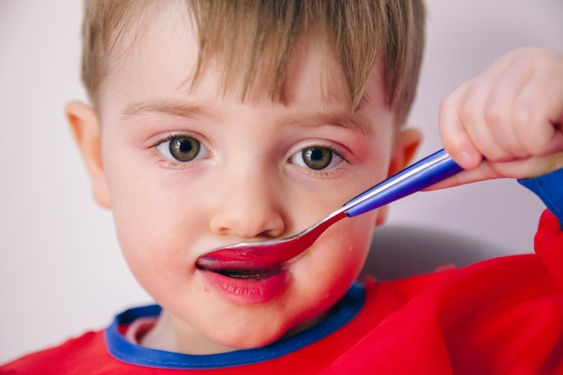 Petit blond caucasien enfant mangeant de la gelée rouge à partir d'une cuillère. mode de vie familial et sain.