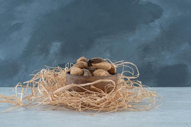 Un petit bol en bois avec des amandes sur du foin.