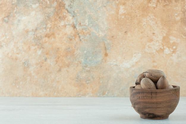 Un petit bol en bois de noix sur fond blanc. photo de haute qualité