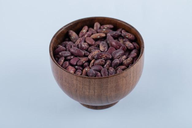Un petit bol en bois plein de haricots rouges crus.