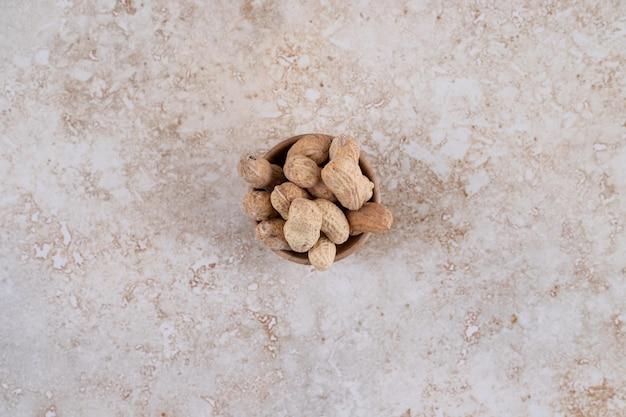 Un petit bol en bois rempli de noix de cajou saines.