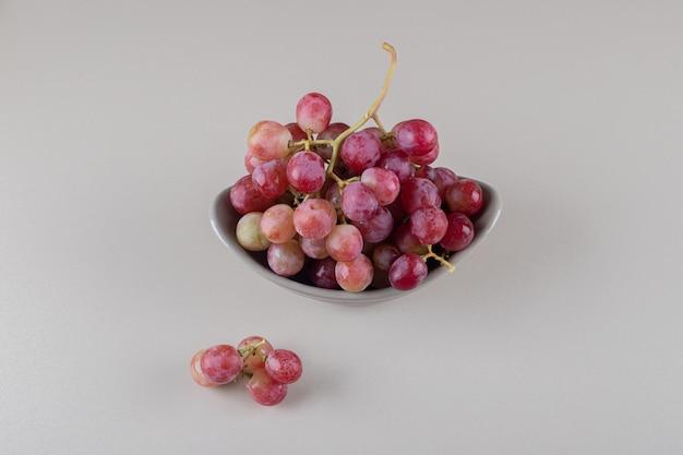 Petit bol avec une grappe de raisin sur marbre