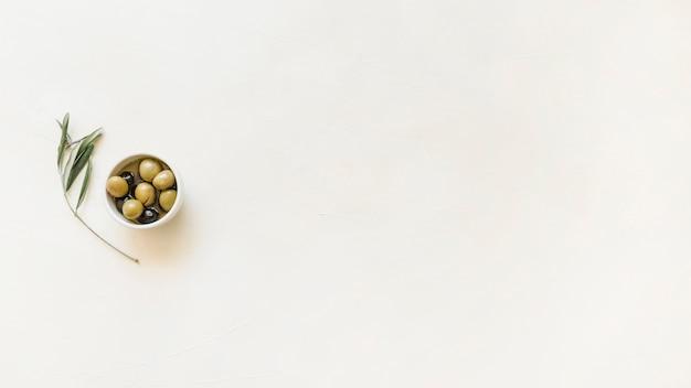 Petit bol avec des olives et des feuilles