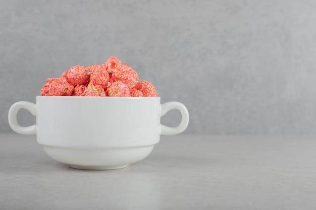 Petit bol rempli de pop-corn enrobé de rouge sur fond de marbre.