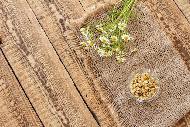 Petit bol en verre avec des fleurs sèches de matricaria chamomilla et des fleurs de camomille blanches fraîches sur un sac et un fond en bois. vue de dessus.