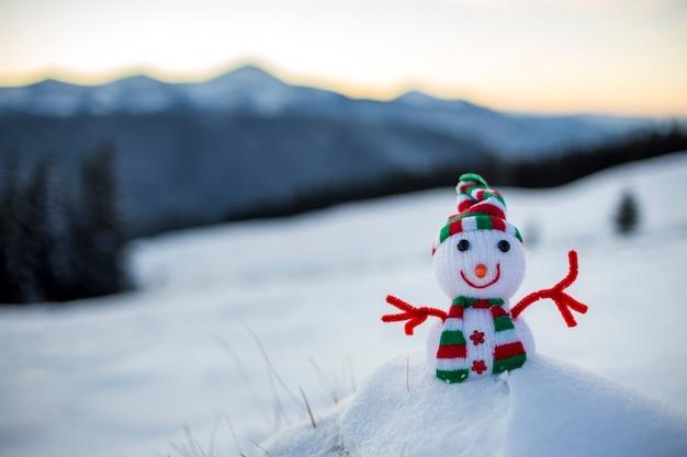 Petit bonhomme de neige de bébé jouet drôle en bonnet et écharpe tricotés dans la neige profonde en plein air sur fond de paysage de montagnes couvertes de neige floue. thème de carte de voeux de bonne année et joyeux noël.