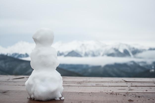 Un petit bonhomme de neige est debout sur une table, à l'arrière-plan, les pics de la montagne